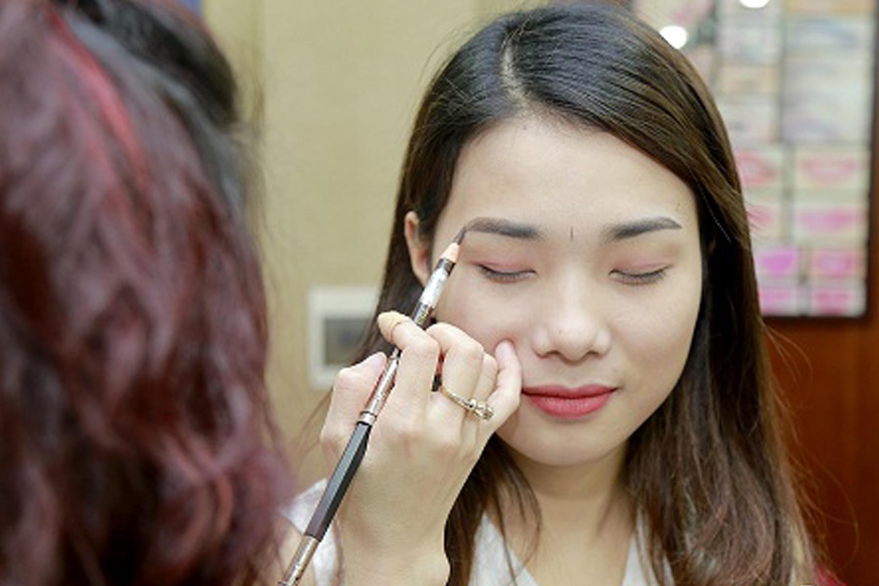 Khách hàng được tạo dáng lông mày trước khi thực hiện phun xăm